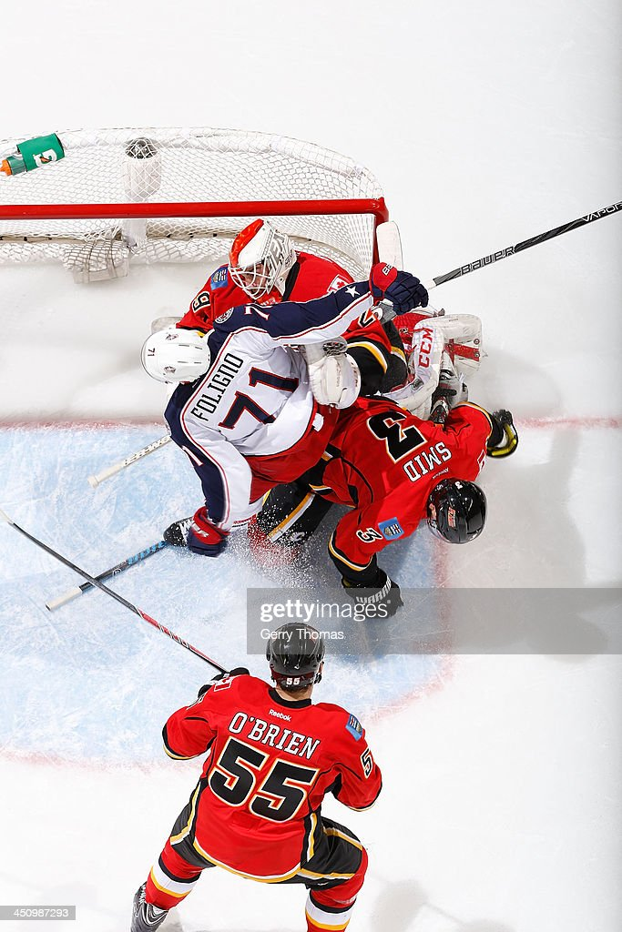 Reto Berra #29, Ladislav Smid #3 and Shane O'Brien #55 of the Calgary Flames defend the net against Nick Foligno #71 of the Columbus Blue Jackets at Scotiabank Saddledome on November 20, 2013 in Calgary, Alberta, Canada.