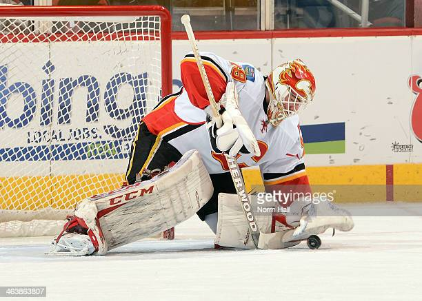 Reto Berra of the Calgary Flames covers the puck with his glove against the Phoenix Coyotes at Jobingcom Arena on January 7 2014 in Glendale Arizona