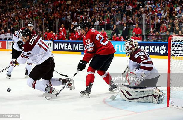 Reto Suri of Switzerland and Kristaps Sotnieks of Latvia battle for position in front of the net during the IIHF World Championship group A match...