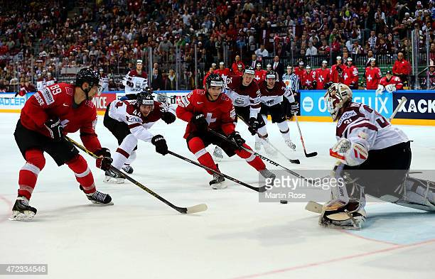 Reto Suri of Switzerland fails to score over Edgars Masalskis goaltender of Latvia during the IIHF World Championship group A match between...