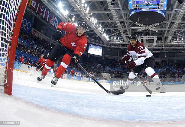 Reto Suri of Switzerland misses a puck passing in front of an open net against Vitalijs Pavlovs of Latvia in the second period during the Men's Ice...