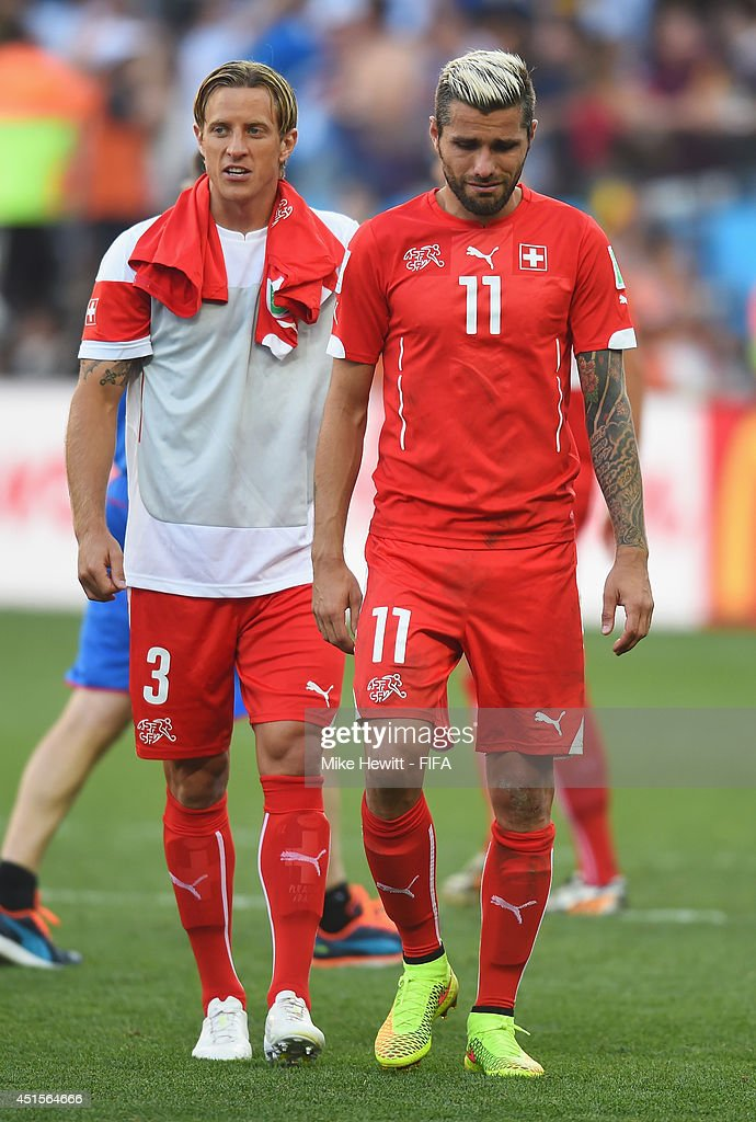 Reto Ziegler of Switzerland (L) and Valon Behrami of Switzerland show their dejection as they walk off the pitch after the 0-1 defeat in the 2014 FIFA World Cup Brazil Round of 16 match between Argentina and Switzerland at Arena de Sao Paulo on July 1, 2014 in Sao Paulo, Brazil.
