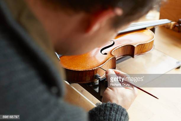 retouching vanish in violin repair workshop - instrument maker stock photos and pictures