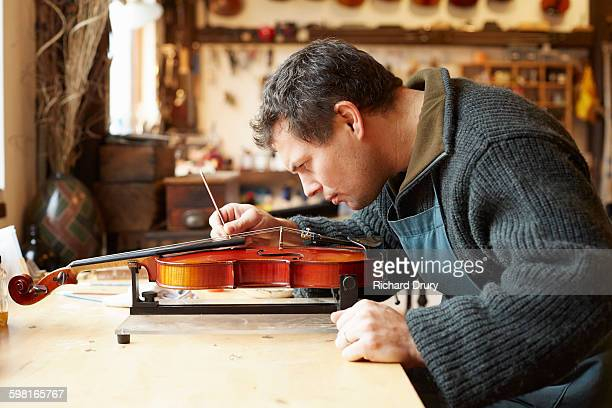 Retouching varnish in violin repair workshop