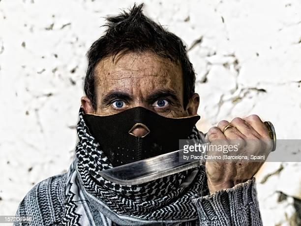 Retrato de hombre con mascara y cuchillo. Agresivo