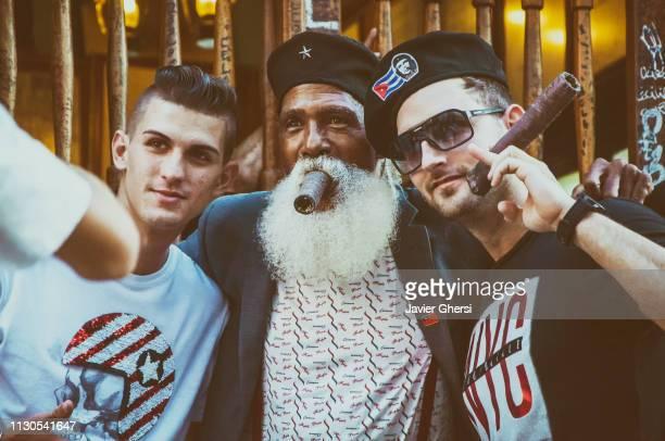 Retrato de hombre cubano y turistas fumando puros