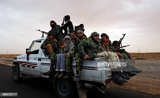 Retreating rebel fighters crowd into the back of a pickup truck leaving Bin Jawwad on Tuesday, Mar. 29, 2011.