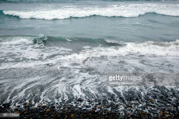 retreating waves on a rocky beach with incoming waves beyond - timothy hearsum stock pictures, royalty-free photos & images