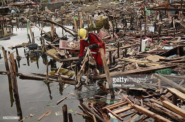 TACLOBAN LEYTE PHILIPPINES NOVEMBER 17 A retrieval team personnel pulls a dead boy out of the water in the aftermath of Typhoon Haiyan on November 17...