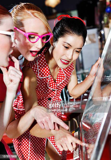 Retro 1950's Young Ladies Choosing Music From Jukebox