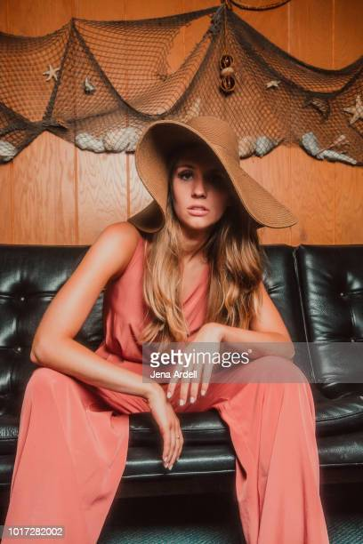 retro 1970s woman wearing sun hat, retro 70s woman wearing beach hat, fashionable woman wearing jumpsuit - pink jumpsuit stock pictures, royalty-free photos & images