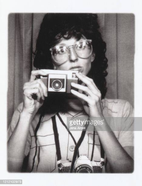 retro 1980s woman with retro eyeglasses holding camera - photography themes stock pictures, royalty-free photos & images