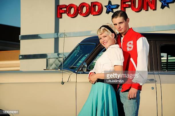レトロな 50 年代のカップルの近くに立つ古い車とディナー