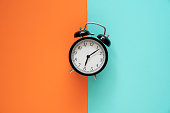 Retro alarm clock on color table background, vintage style