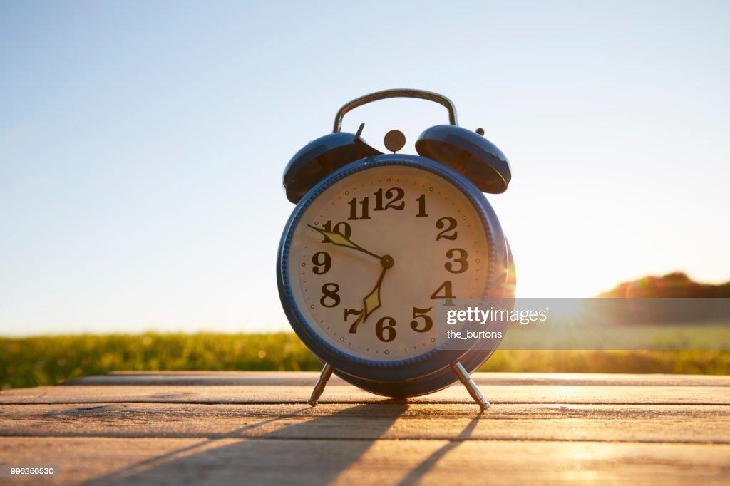 Retro alarm clock on wooden table in garden against sky : Stock Photo