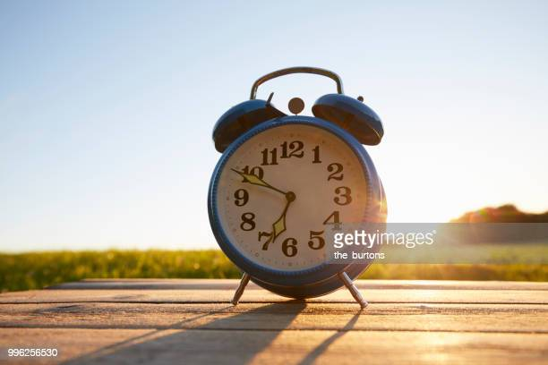 retro alarm clock on wooden table in garden against sky - countdown clock stock-fotos und bilder