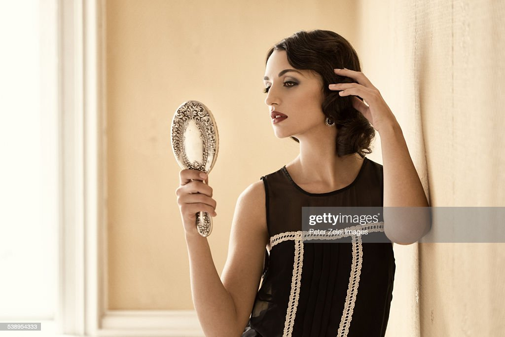 Retro beauty adjusting her hair in a silver mirror : Stock Photo