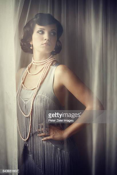 Retro beauty in vintage dress by the window