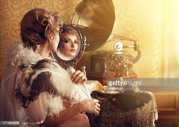 retro beuty with feather fan listening music in boudoir