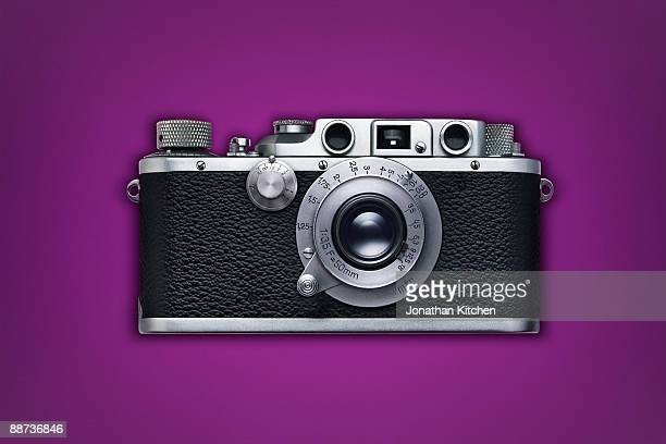 Retro camera on coloured background
