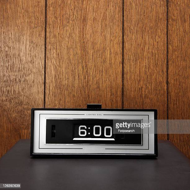 Retro clock set for 6:00 against wood paneling.