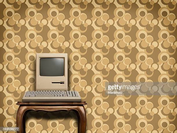 Retro computer on wooden table with sixties wallpaper
