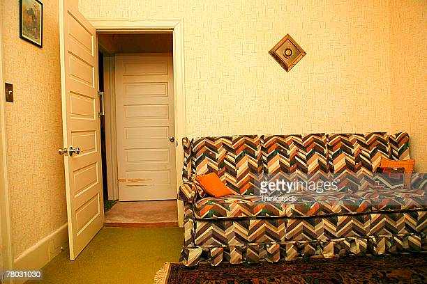 a retro couch against a wall in a room with an open door. - kitsch stock pictures, royalty-free photos & images