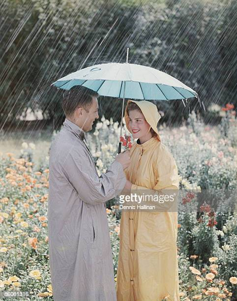 retro couple standing in flower field in the rain - vintage raincoat stock photos and pictures