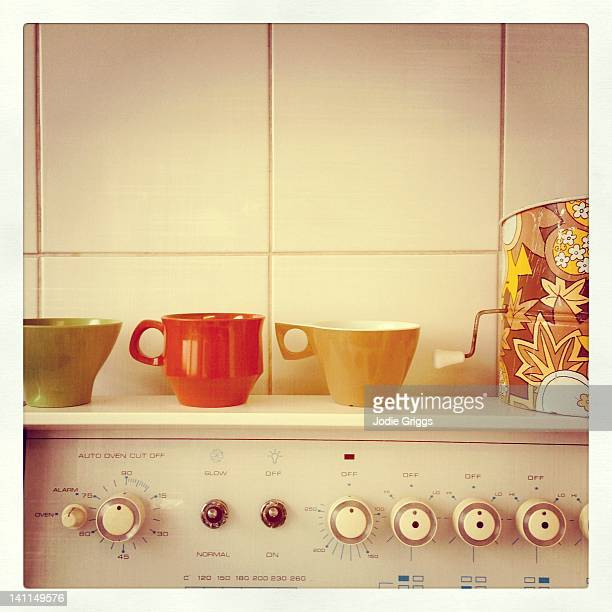 Retro cups & flour sifter sitting on old stove top
