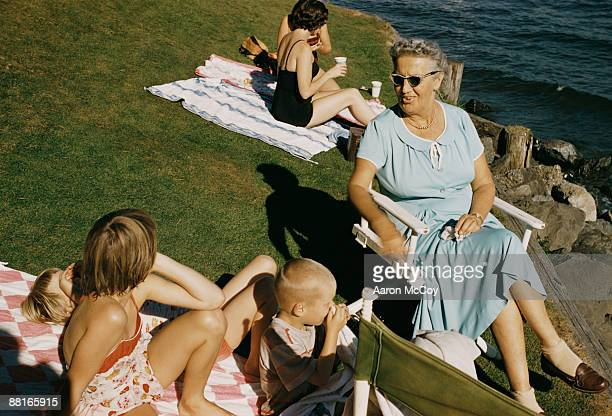 Retro family relaxing by lakeside