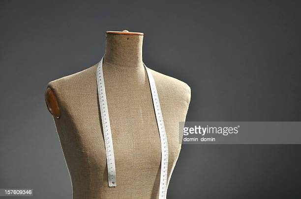 Retro female tailor's mannequin torso with measuring tape, dark background