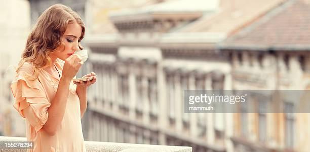 retro Mädchen trinken Kaffee auf dem Balkon