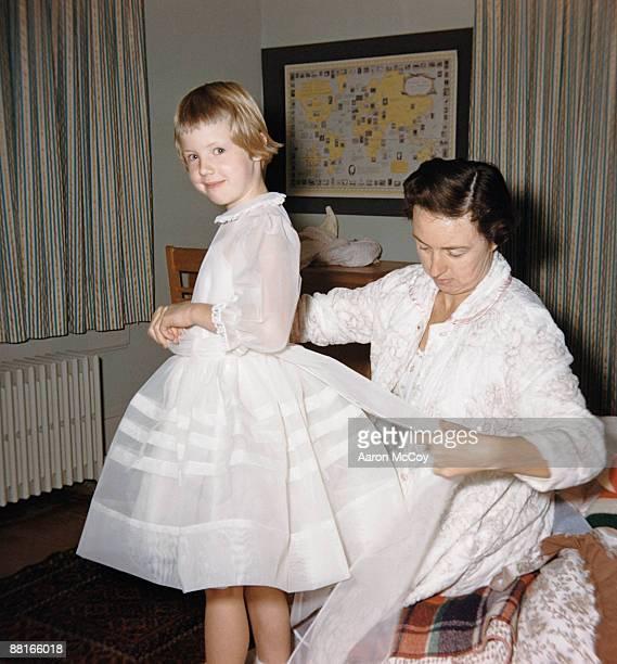 retro girl smiling while mother ties bow in back of dress - catolicismo fotografías e imágenes de stock