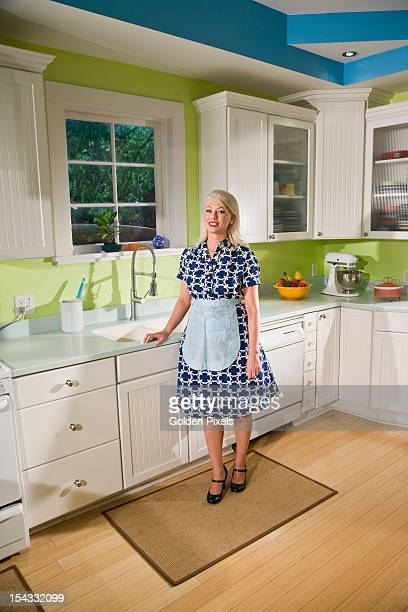 Retro housewife in kitchen wearing apron