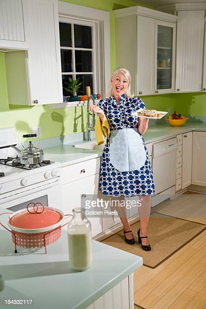 Retro housewife in kitchen with cookies