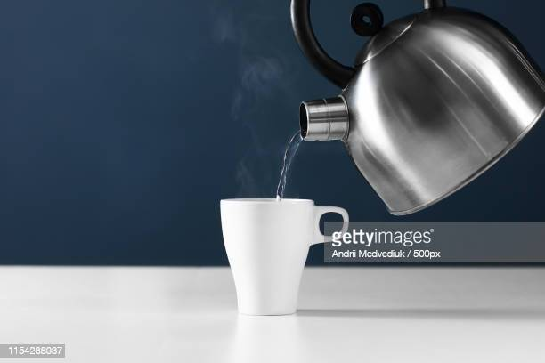 retro kettle pouring water into a cup on a white background with smoke on wood table - boiling stock pictures, royalty-free photos & images