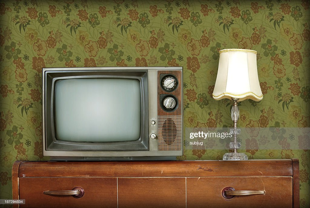 Retro living room with a TV and a lamp atop a wooden desk : Stock Photo