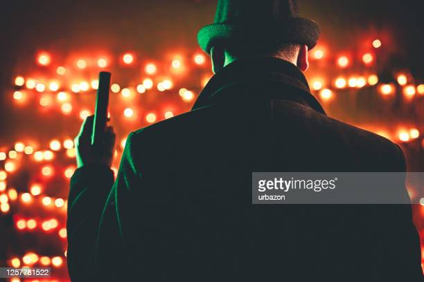 retro man in coat and hat holding a gun - organized crime stock pictures, royalty-free photos & images