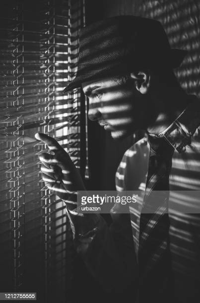 retro man with hat looking through window - film noir style stock pictures, royalty-free photos & images