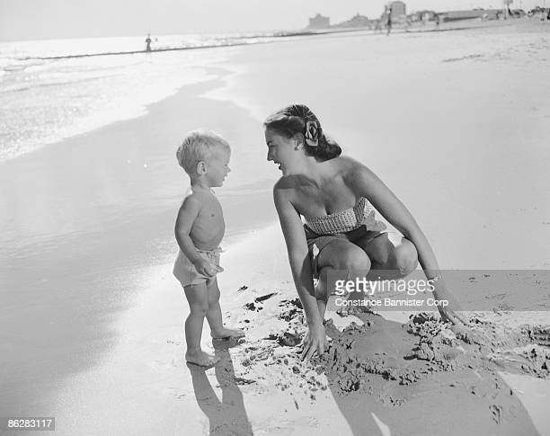 Retro mother and son playing with sand on the beach