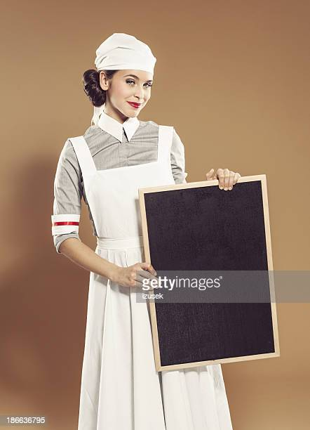 retro nurse holding black board - nursing slogans stock photos and pictures