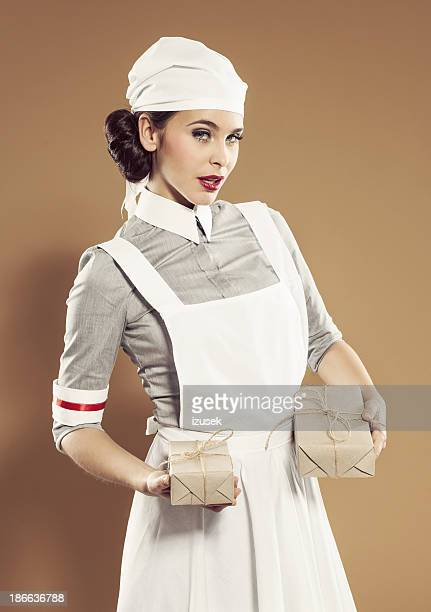 retro nurse holding ration boxes - 1940s erotica stock photos and pictures