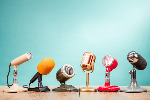 Retro old microphones for press conference or interview on table front gradient aquamarine background. Vintage old style filtered photo 1054657186