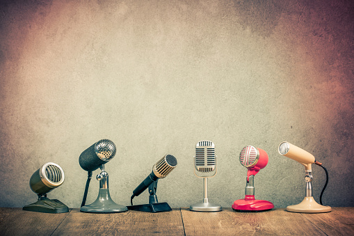 Retro old microphones for press conference or interview on wooden desk. Vintage instagram style filtered photo 1065772700