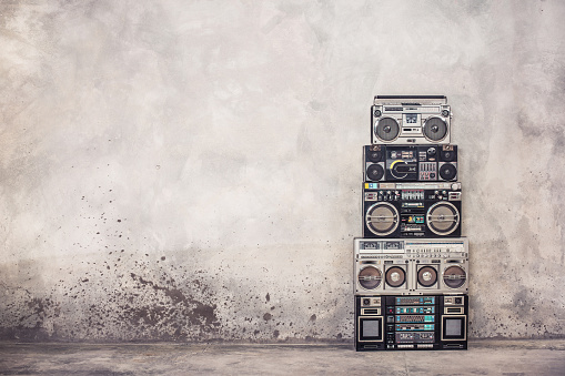Retro old school design ghetto blaster boombox stereo radio cassette tape recorders tower from circa 1980s front concrete wall background. Vintage style filtered photo 1043628624