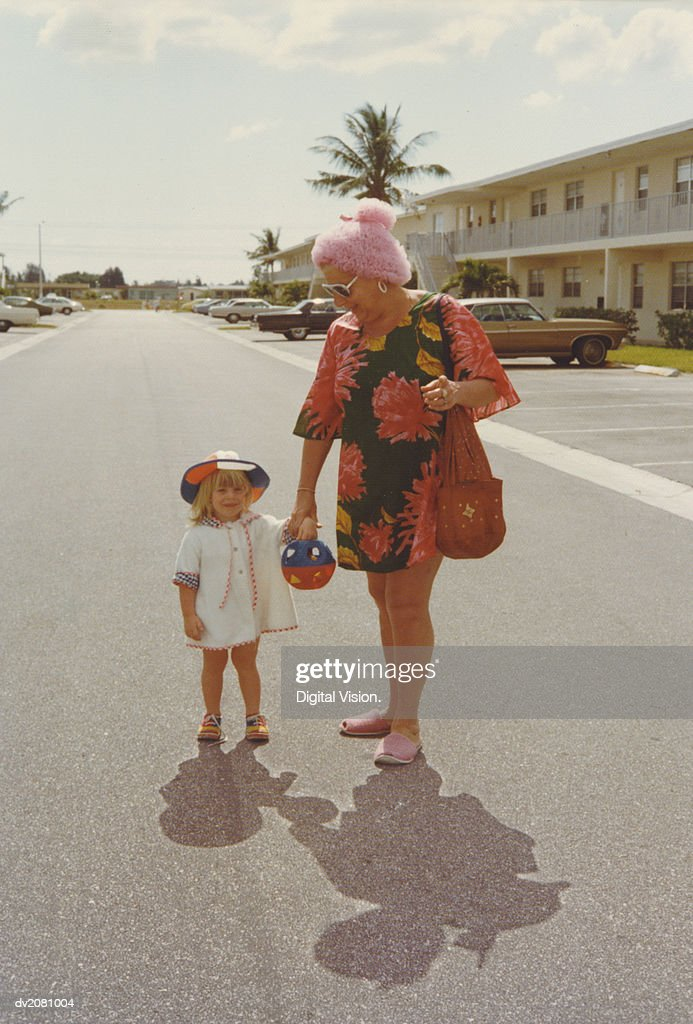 Retro Photograph of a Grandmother and Granddaughter Standing in the Street Holding Hands : Stock Photo