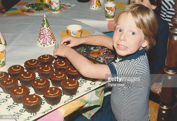retro photograph of a young boy at a birthday party, sitting at a table with a tray of cupcakes - happy birthday vintage stockfoto's en -beelden