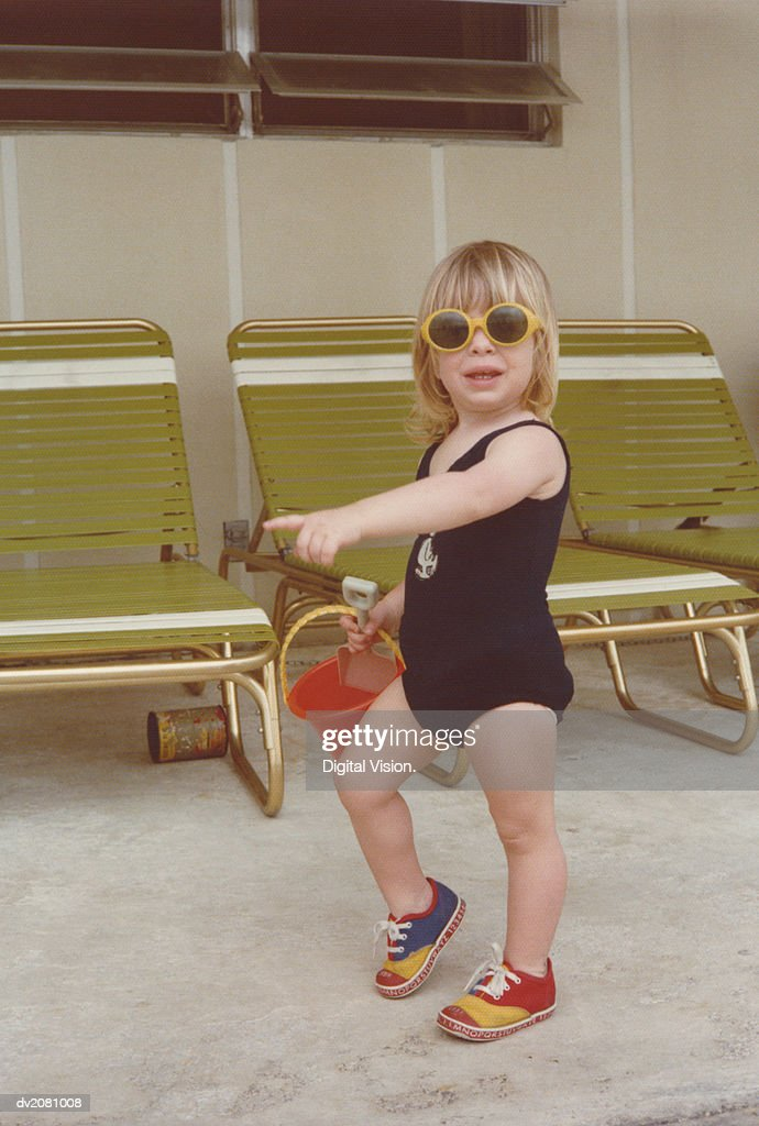 Retro Photograph of a Young Girl in a Swimming Costume, Carrying a Bucket and Spade : Stock Photo