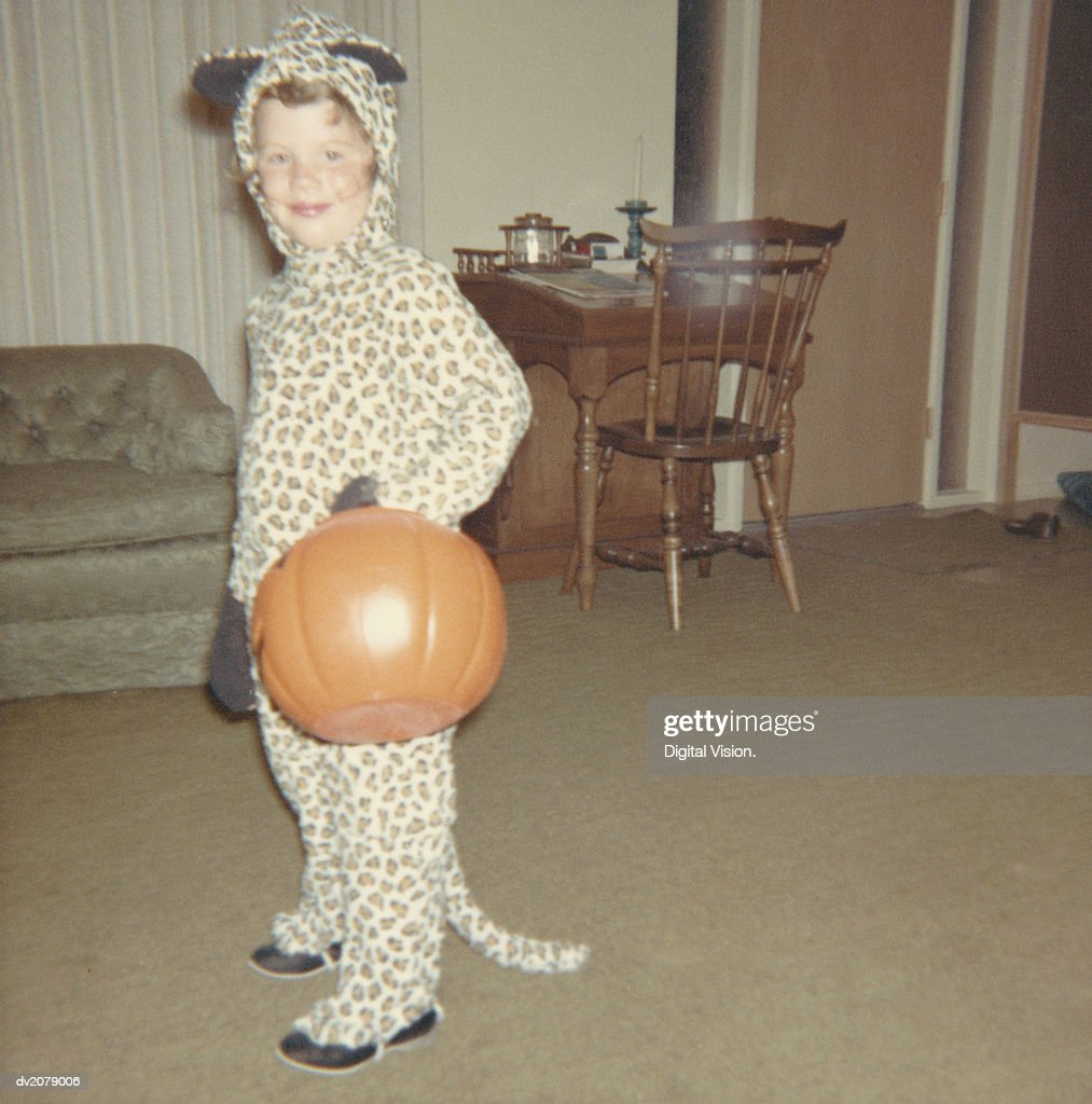 Retro Photograph of a Young Girl in Trick or Treat Fancy Dress, Carrying a Pumpkin : Stock Photo