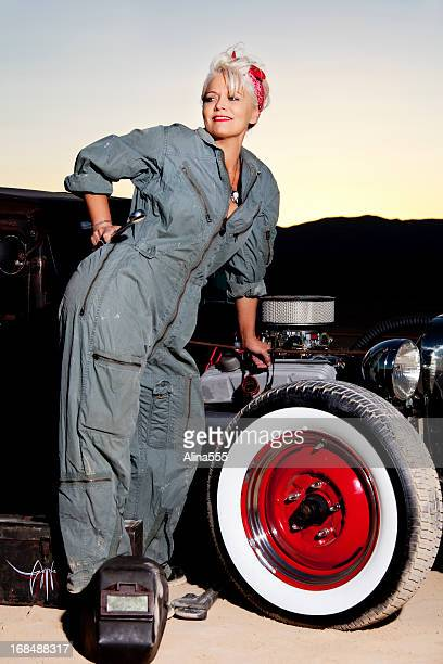 Retro pinup girl in mechanic's coveralls by a classic car